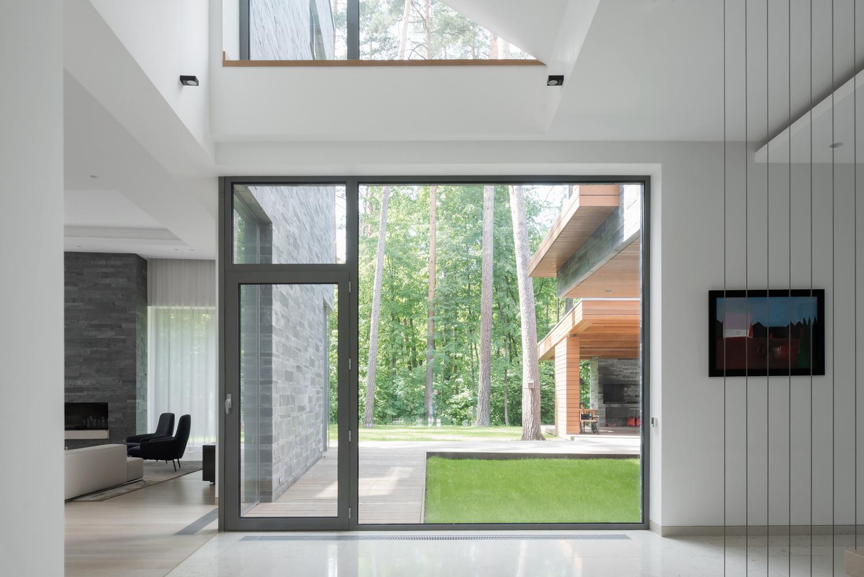 【住宅设计】两兄弟之家,营造现代版花园城市起居室的窗朝向树林.