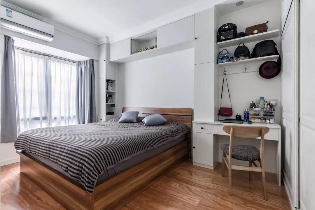 主卧室的床头背景墙和沙发背景墙做法类似,用柜子来代替床头柜,上方还