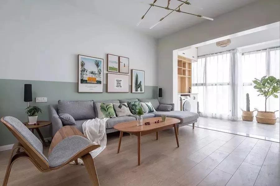客厅的采光非常好,背景墙上是撞色系,上面是白色的,下面是薄荷绿的